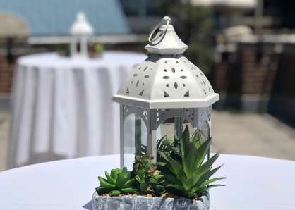 Closeup of a pot of succulents and a white lantern on a cocktail table on the terrace. The Philadelphia skyline can be seein the background, reflected in tthe mirrored surface of One Liberty Place.