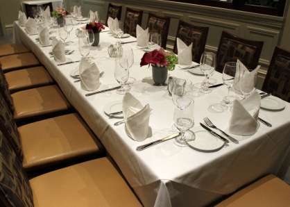 Closeup of a long, 20-person table, with full place settings, cloth napkins, and flowers in the Wine Room and