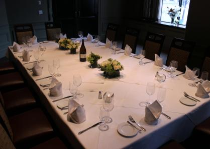A room with glass-doored wine refrigerators in the walls and sheer curtains for privacy on one end. A long table is set for 16 and surrounded by high-backed chairs