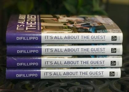 A stack of four hardback copies of Steve DiFillippo's book, It's All About the Guest