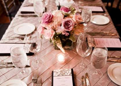 Rectangular tables set with individual menus, centerpiece bouquets of pink roses