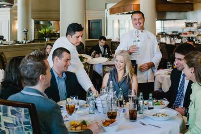 Five people enjoy dinner and drinks in the open Davio's Boston dining room, while servers pour water and bring additional dishes