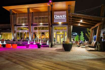 The fountains outside Davio's King of Prussia lit with magenta lights as diners enjoy the evening on the patio