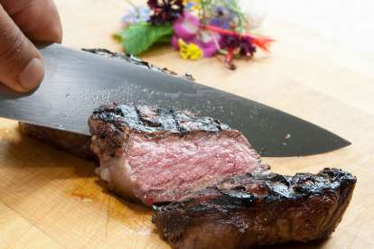 A hand holds a chef's knife carving a medium rare steak