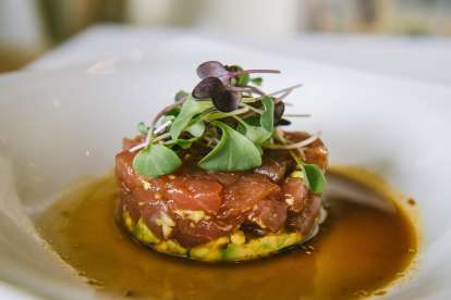 Tuna tartare with avocado and microgreens in a soy mustard sauce