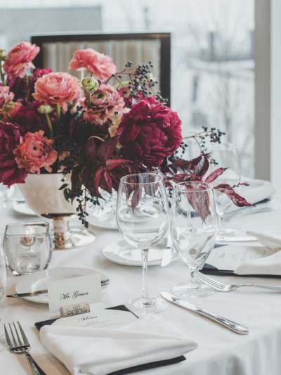 A numbered table with individual place cards and menu, a low centerpiece of a silver bowl of peonies and other flowers in various shades of pink