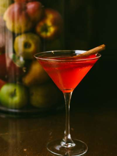 apple martini in martini glass with cinnamon stick and apples behind photo