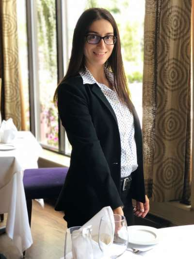 Francesca Little, a woman with long brown hair and glasses and wearing a black pantsuit, adjusts a place setting in a Davio's private dining room