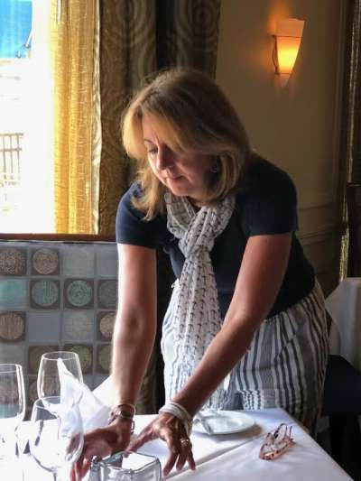 Gia Page, a Caucasian woman with blonde hair and wearing a navy top, navy and white striped pants, and a patterned scarf around her neck, adjusts a table setting next to a sunny window in Davio's Lynnfield