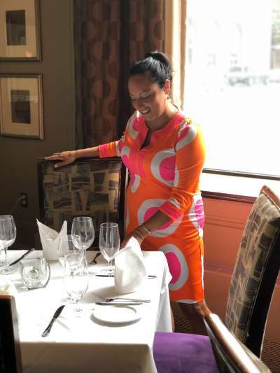 Jess Phifer, wearing a bright orange, white, and hot pink dress, arranges a place setting in the dining room