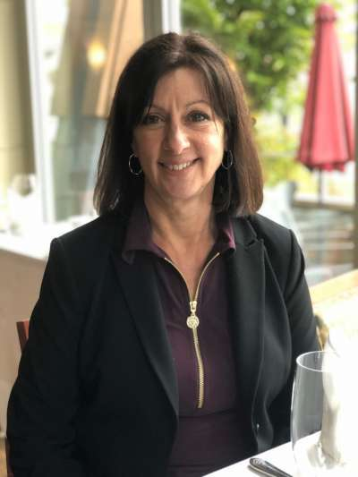 Julie Millard, a Caucasian woman with shoulder-length brown hair, sits wearing a black jacket and a dark purple top with a gold zipper at the neck, the Davio's King of Prussia patio visible in soft focus through the window behind her