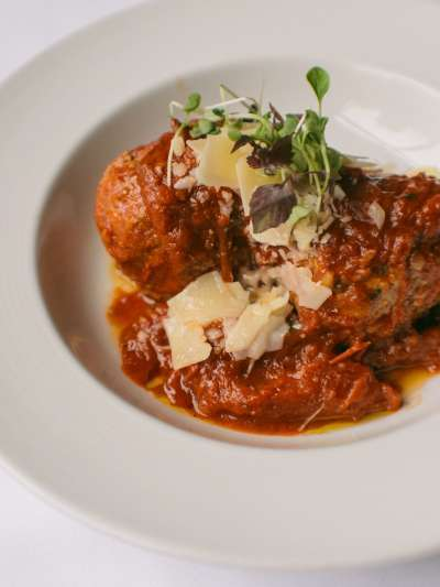 Meatballs in chunky tomato sauce with shaved parmesan cheese and garnished with microgreens