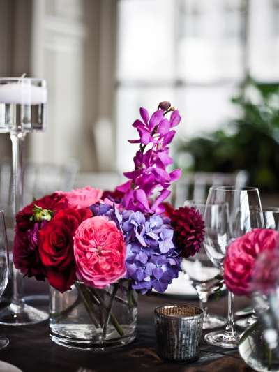 Brightly colored purple, pink, and red flowers are arranged in a glass vase, surrounded by wine glasses and votive candles. A large window is in soft focus in the background.