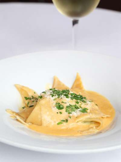 Lemon Ricotta Ravioli with Lemon Butter Sauce served with a glass of white wine