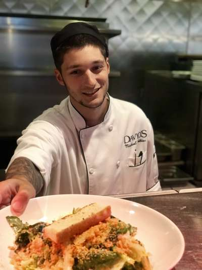 Mike Pothier, in chef's whites and a black cap, smiles in the Davio's kitchen as he places a finished dish on the counter