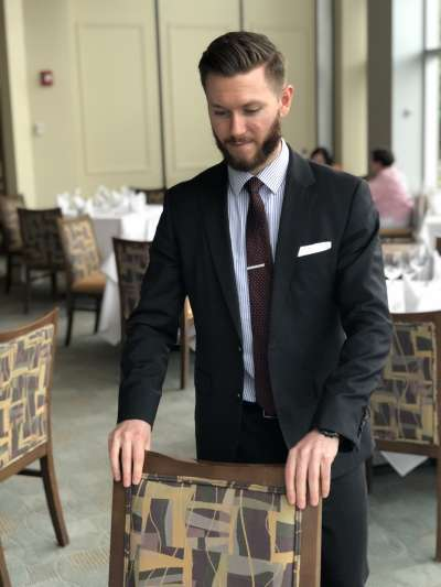 Nathan McKearney, a Caucasian man with brown hair and close-cropped beard, wears a dark suit with blue striped shirt and maroon tie as he adjusts a chair in the dining room