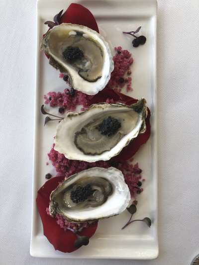 Three oysters on the half shell with caviar, on a bed of rose petals