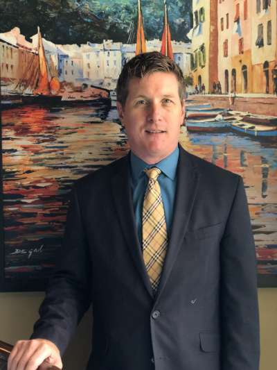 Paul Dunn, in a dark suit with blue shirt  and yellow tie, stands in front of a colorful painting of a Mediterranean town on the water