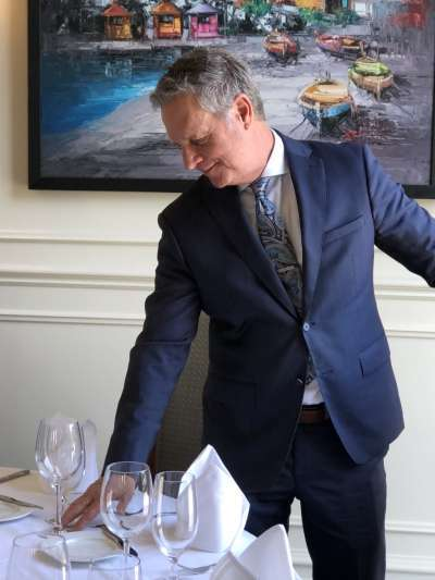 Scott McCully, a Caucasian man with grey hair, wears a blue suit and paisley tie as he leans to adjust a place setting in the Davio's Irvine dining room