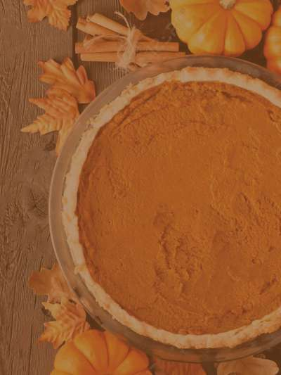 Top view of a pumpkin pie on a wooden table, surrounded by miniature pumpkins, fall leaves, and a bundle of cinnamon sticks
