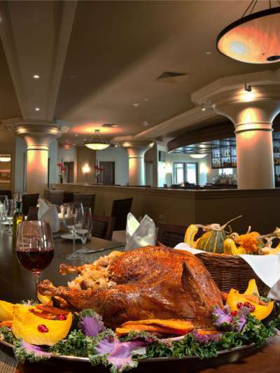 A roast turkey on a platter with winter squash, cranberries, and kale sit on a long table inside Davio's. A glass of wine and basket of gourds are seen behind the platter.