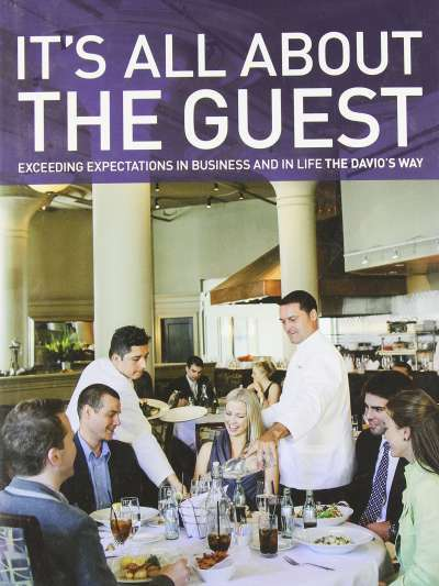 Cover of Steve DiFillippo's book, It's All About the Guest, showing a smiling group of guest being served in the Davio's Boston dining room