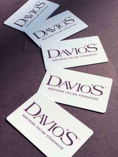 Five white plastic gift cards featuring the Davio's logo in purple, fanned out on a dark background