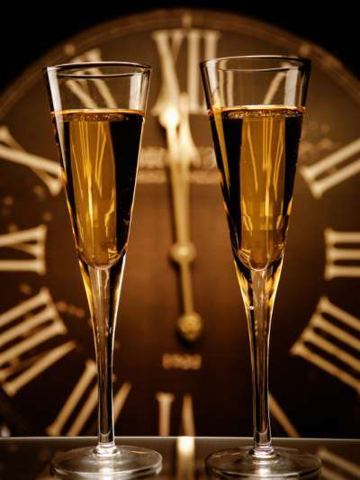 Two flutes of champagne in front of a large clock with roman numerals, hands pointing to one minute before midnight