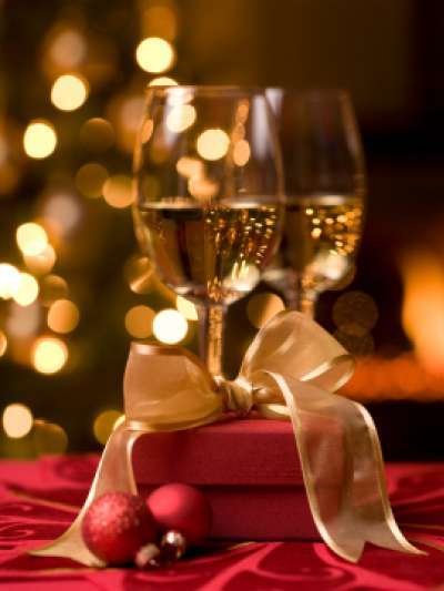 Two glasses of white wine, a red gift box tied with gold ribbon, and two small red ornaments sit on a red tablecloth, with a Christmas tree with white lights and a fire in a fireplace out of focus in the background