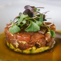 Tuna tartare with avocado and soy mustard, garnished with microgreens