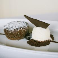 An individual-sized warm chocolate cake, disted with powdered sugar, sits next to a scoop of vanilla bean ice cream topped with a triangular piece of dark chocolate.