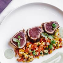 Three medallions of seared tuna, plated with a relish of fresh corn, tomatoes, and cucumbers