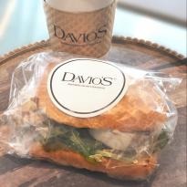 A chicken salad sandwith with greens, wrapped in cellophane and sealed with a Davio's sticker, accompanied by a to go cup of coffee with a Davio's cardboard sleeve