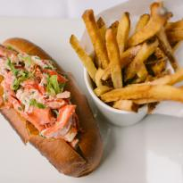 A lobster roll stuffed with large chunks of Maine lobster in a lemon chive mayo, accompanied by crispy fries in a cup