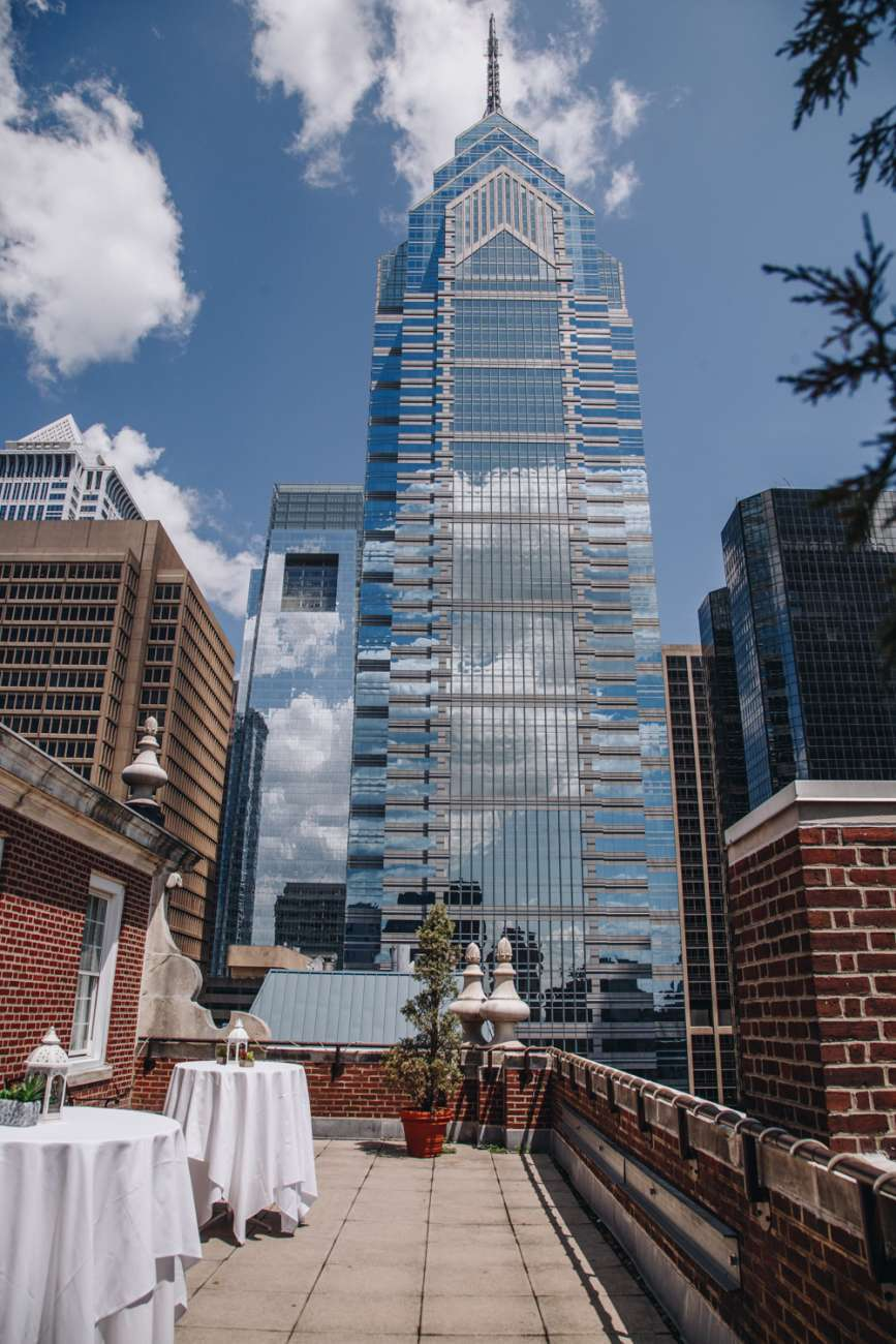 The Skyline Patio with One Liberty Place against a blue sky filled with fluffy clouds in the background