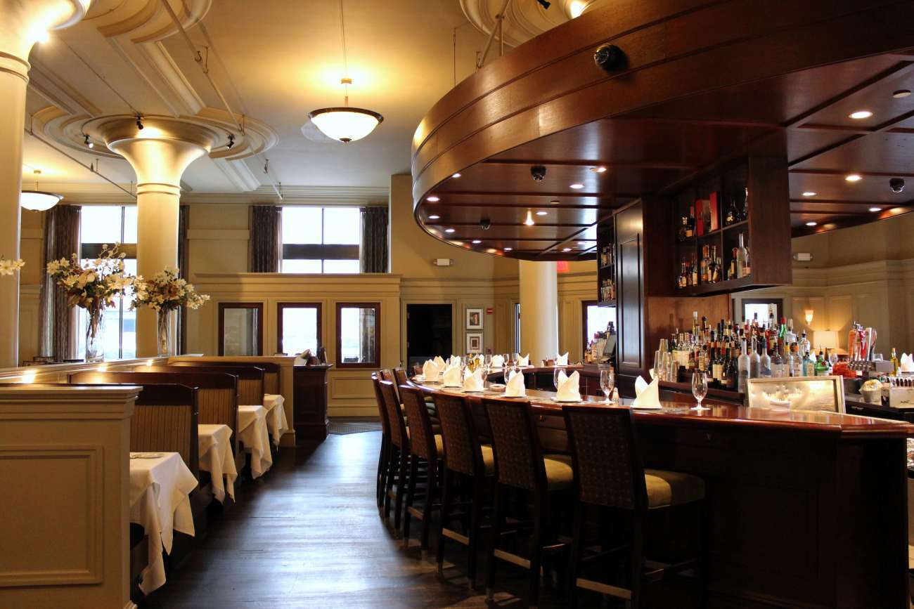 View of the main dining room with booths on the left and oval-shaped bar on the right. The room features high ceilings with pendant lights, tall windows, and Davio's signature columns.