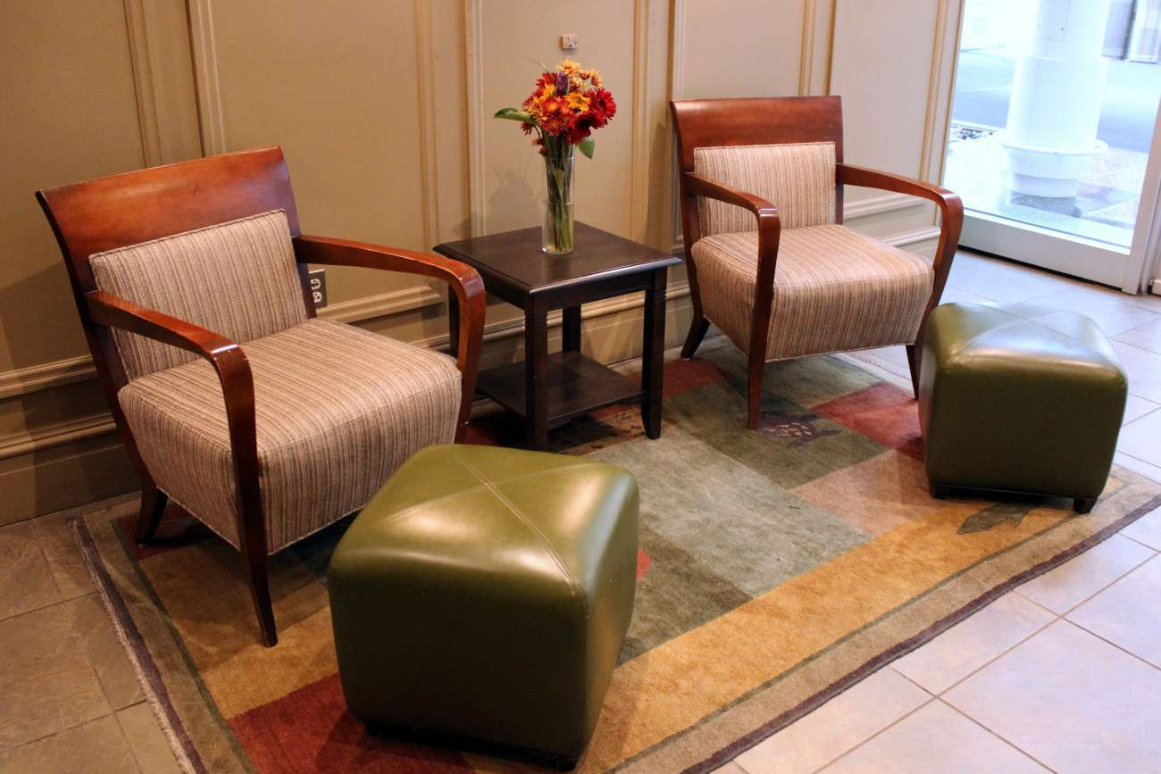 Two armchairs and green leather ottomans with an occasional table and floral arrangement in between, on a brightly patterned rug