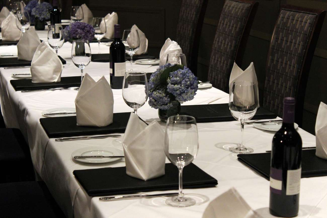 Closeup of long table set with menus, napkins folded into crown shapes, and blue hydrangea centerpieces