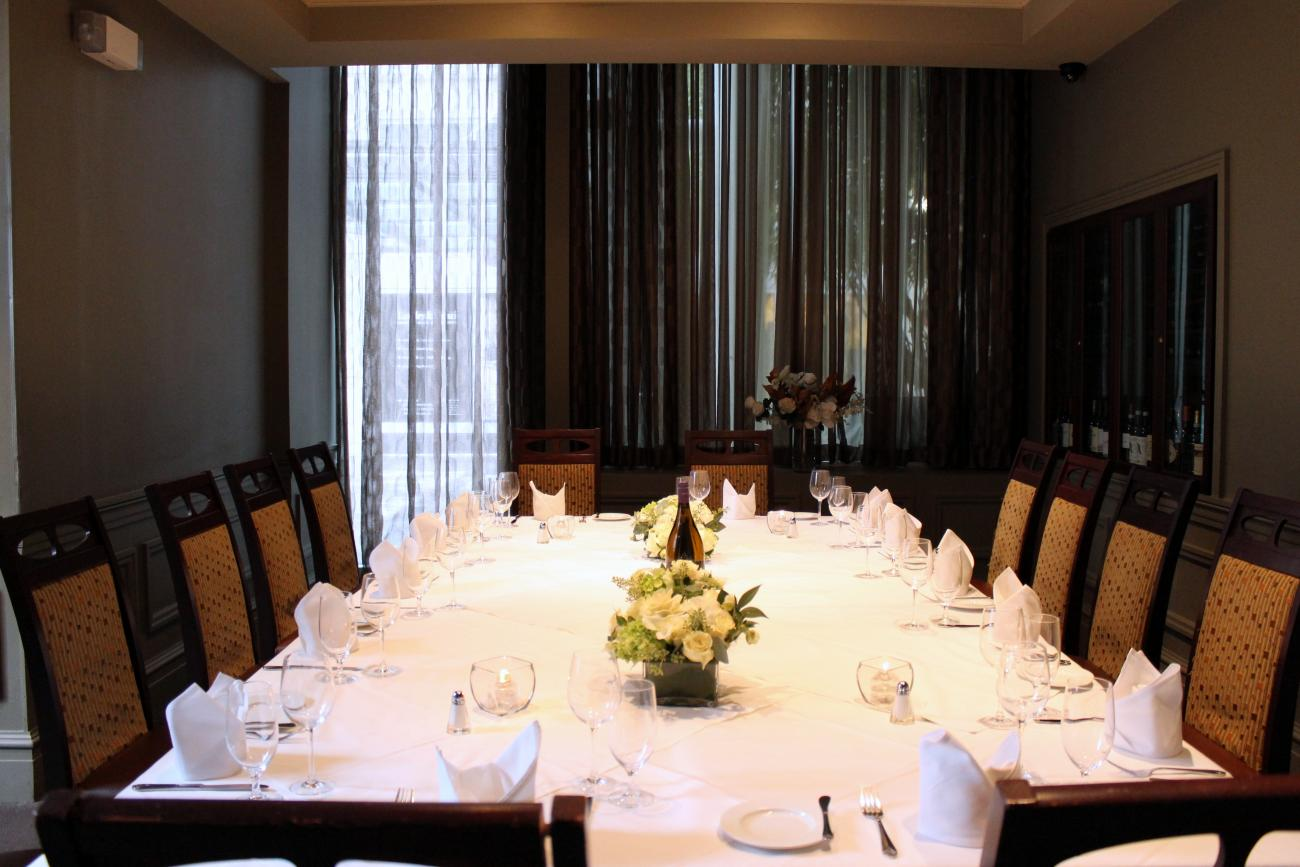 A room with glass-doored wine refrigerators in the walls and sheer curtains for privacy on one end. A long table is set for 16 and surrounded by high-backed chairs with upholstered backs