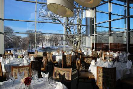 Floor-to-ceiling windows show winter trees and a bright blue sky, round tables and high-backed chairs seat up to 64