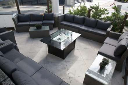Modern wicker sofas with deep gray cushions surround the outdoor fire pit, seating 10–20 guests