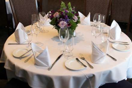 Closeup of a round table set for six, with white tablecloth, cloth napkins, and wineglasses. The centerpiece is an arrangement of lavender roses, purple foxgloves, purple hydrangea, and greenery.
