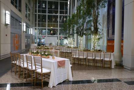 Long tables with white tablecloths and gold chairs, white floral arrangements, potted trees wrapped with white lights, and a stories-high window create the perfect setting for a holiday event