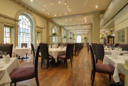 The main dining room features high arched windows and seats 150 with space for dancing and mingling