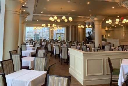 The main dining room features high ceilings, majestic columns with period cornice moldings, large wall-to-wall windows overlooking Boston Harbor with beautiful views of the ocean, warm wood tones with inviting wall colors.