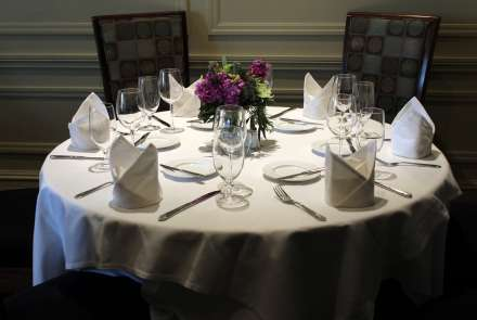 A round table set for six with a floral centerpiece