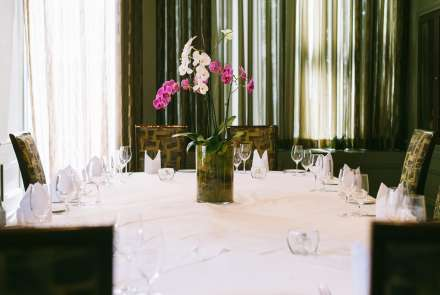 Table set for eight with white tablecloth and a centerpiece of pink orchids