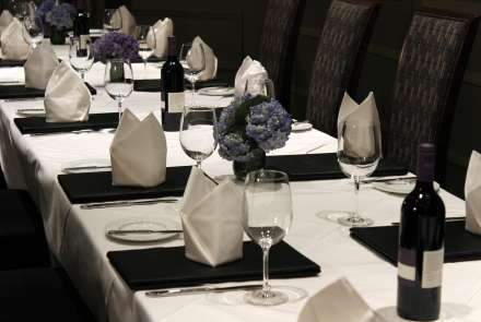 Closeup of a table setting with cloth napkins, wine, and hydrangea centerpieces