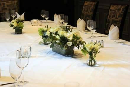 Closeup of white flowers in low vases on a white tablecloth. The table is set with glasses, silverware, and white napkins