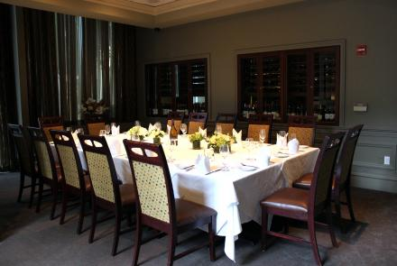A room with glass-doored wine refrigerators in the walls and sheer curtains for privacy on one end. A long table is set for 16 and surrounded by high-backed chairs with leather seats